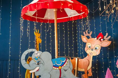 Childrens rides close-up and copy space. Childrens carousel with animals in an amusement park.