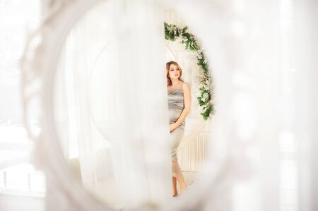 Beautiful pregnant woman in a bright interior under Christmas. Pregnant and Christmas decorations in the Scandinavian style. Woman on New Years swing Stockfoto