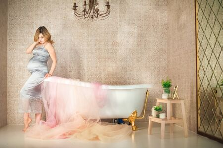 Pregnant woman in the bathroom. A pregnant woman near the bath strokes her belly close-up and copy space. Stockfoto