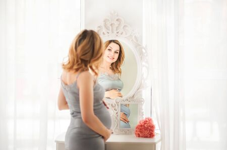 Pregnant woman in a white canopy bedroom. Pregnant near white dressing table close-up and copy space. Stockfoto
