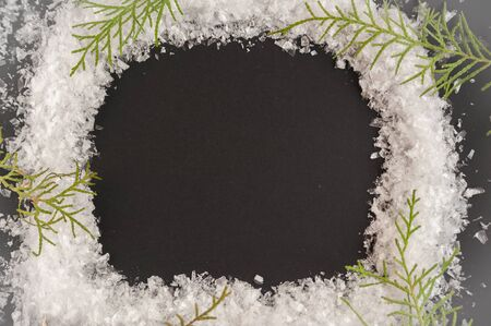 Flat lay christmas picture. A wreath of snow on a black background.