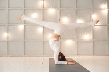 Woman is practicing yoga in a bright studio. Woman and yoga asanas. Stock Photo