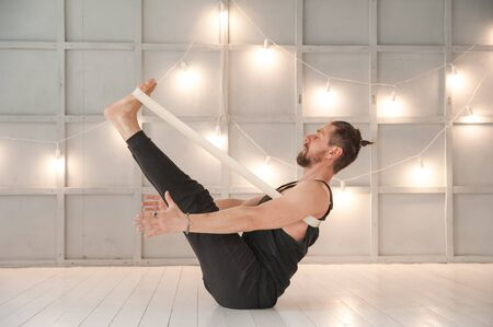 A man practices yoga in a bright studio. Man and yoga asanas with elastic. Stockfoto - 135495068