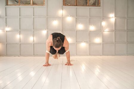 A man practices yoga in a bright studio. Man and yoga asanas with elastic. Stockfoto - 135494951