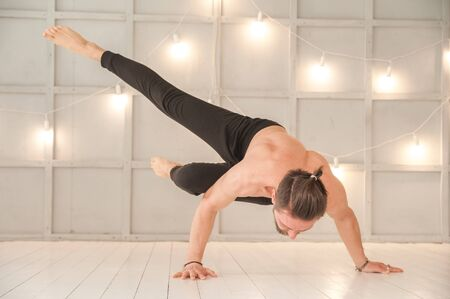 A man practices yoga in a bright studio. Man and yoga asanas with elastic.