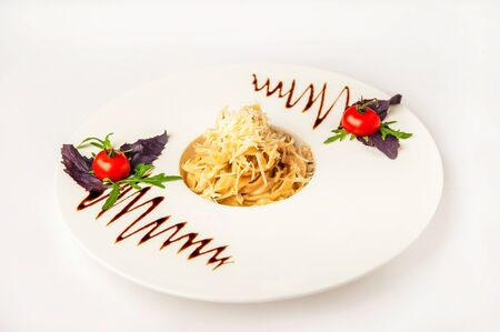 Pasta with sauce and tomatoes in a restaurant close-up. Italian pasta with microgreens on a white plate and copy space. Reklamní fotografie