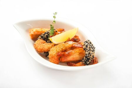 Shrimp in a restaurant close-up. Tiger prawns breaded on a white plate and copy space.