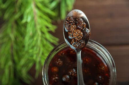 Siberian dessert - young pine cones jam. Ukrainian cone jam in a jar on a dark background close-up and copy space. Fritters with jam on a plate. Pancakes with jam.