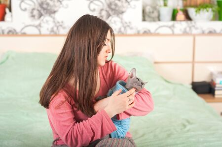 Girl with a cat in the bedroom on the bed. Young woman kisses and hugs the Sphinx at home close-up and copy space. Pets and people. Stock Photo