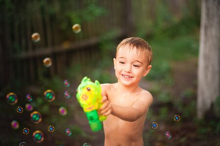 Boy playing with soap bubbles plan and copy space. The boy in the summer shoots a water pistol. Kids games with water and bubbles in the backyard.