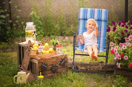 Boy sells homemade lemonade close-up and copy space. The boy in the summer makes homemade lemonade. Childrens games with lemonade in the backyard. Stockfoto