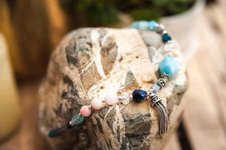 Bracelets made of natural stones on textured stones. The mysticism of amulets. Esoterics in handmade bracelets close-up and copy space.