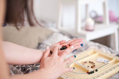 Bracelets made of natural stones. Girl creates handmade jewelry close-up. The mystic of amulets, beads.