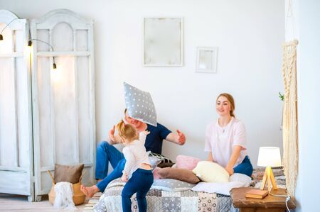 Happy family at home. Fathers Day and Mothers Day. Mom, dad and daughter in a rustic style interior. Stockfoto