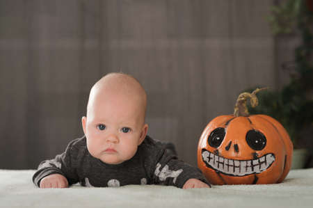 My first Halloween. Small child and pumpkin. Autumn concept, halloween, bats, pumpkins, newborn close-up and copy space.
