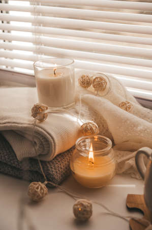A cozy and warm hygge concept with white sweaters, candles, a cup, a garland on the windowsill. Autumn trends 스톡 콘텐츠 - 155078780