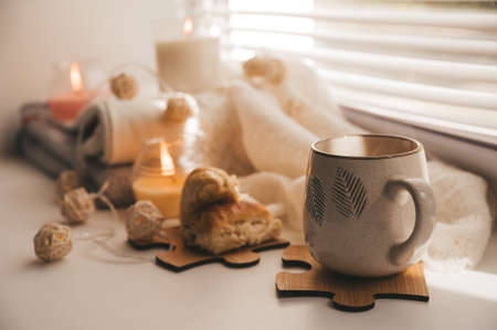 A cozy and warm hygge concept with white sweaters, candles, a cup, a garland on the windowsill. Autumn trends