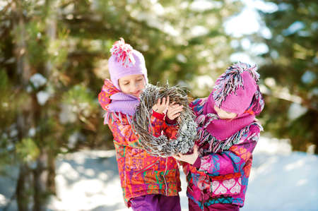 Two sisters in winter in a snowy forest holding a christmas wreath 스톡 콘텐츠