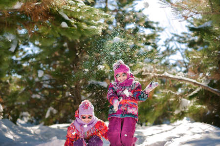 Two sisters in winter in a snowy forest playing in the snow