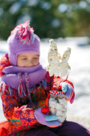 Little girl in winter in a snowy forest drinks hot cocoa. Christmas drink and snowman
