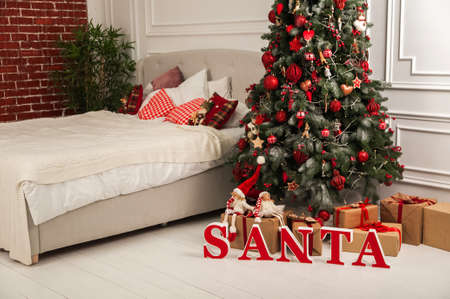 New Year's decor of the bedroom in the Scandinavian style. Christmas tree, Santa Claus and bed with pillows. Hygge New Years concept. 스톡 콘텐츠