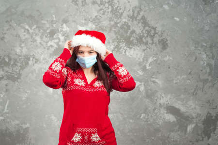 Girl in a Santa Claus hat on a background of a concrete gray wall close-up and copy space. Young woman in a New Year's costume and a face mask from COVID 2019. 스톡 콘텐츠