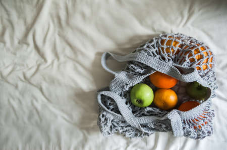 Gray mesh bag with yellow oranges close-up and copy space. Handmade eco bag on textiles