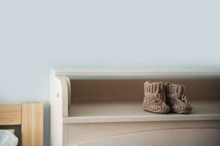 Baby booties on the shelf and copy space. Knitted boots for a newborn on a chest of drawers close-up. 스톡 콘텐츠