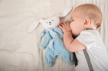 Newborn toddler with a toy on the bed close-up and copy space. The child sleeps on a large bed in the bedroom.