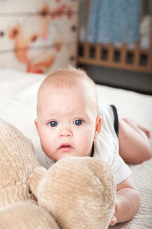 Newborn toddler with a toy bear on the bed close-up and copy space. Funny baby and soft toy bear at home in the bedroom. 스톡 콘텐츠