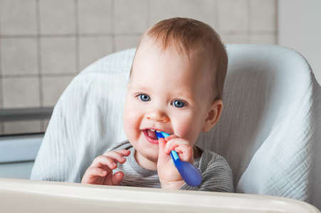 Cheerful child eats food with spoon. Close up portrait of happy boy in high chair. Complementary feeding, food, infant. concept of childhood, care, first lure and baby food. first feeding of baby. Inf