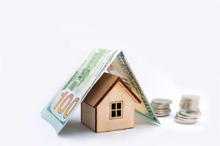 Investment real estate concept. Mortgage concept for money house made of coins. House Model Money White Background Savings Plans Housing Finance Banking. wooden house model on pile of Euro banknote