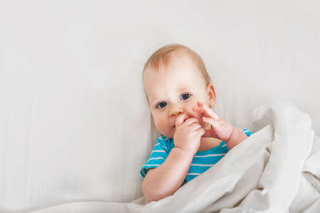 Portrait of baby 11 months old on bed close up. Funny kid on white cloth. Restful sleep concept, teething, baby care.