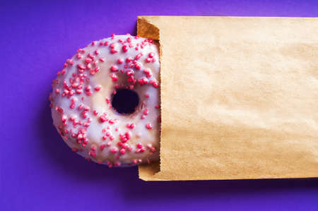 Donut with purple and pink powder close-up on blue background. Food delivery concept, donut in kraft wrapping paper and copy space.