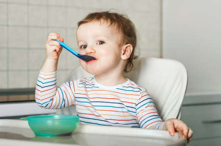 The child eats and holds spoon with fruit, vegetables puree, healthy food for child. Complementary feeding of child. 스톡 콘텐츠