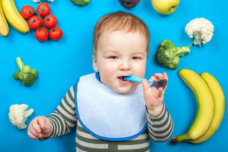Child with vegetables and fruits on blue background, healthy baby food. Baby food, bananas, broccoli, cauliflower, zucchini, apples, tomatoes 스톡 콘텐츠