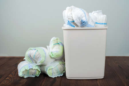 Diapers waste, dirty diapers in garbage pail Disposing of used baby nappies. Environmental Impact of Disposable Diapers. Pollution of the environment, soil and water
