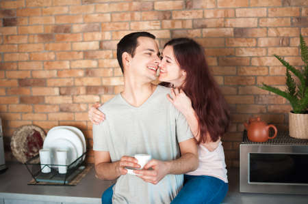 Lovers hug in kitchen. Breakfast on St. Valentine's Day. Self-isolation, stay at home. 스톡 콘텐츠