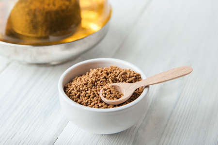 uncooked buckwheat in white plate and wooden scoop, on a white background close-up. Buckwheat tea and granules. Tea in transparent teapot. Space for text.