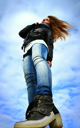 foreshortening: Young woman on windy beach, Ukraine. Foreshortening from below.