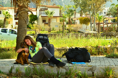 guarding: Dog and girl guarding the backpack under the palm tree. Turkey, Antalya.