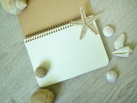 Notepad with marine objects on the wooden surface.