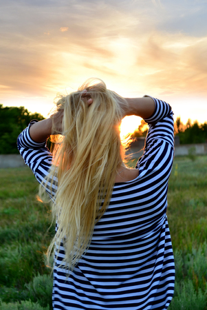 Happy young woman in rays of sun. Stock Photo