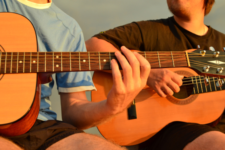 Friends playing guitar at the seacoast. Stock Photo