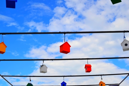 Colorful nesting boxes on blue sky.