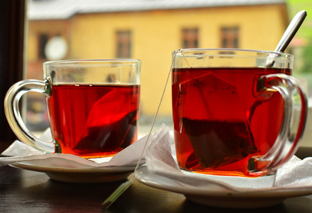 Two cups of hot tea on the table in the window background.