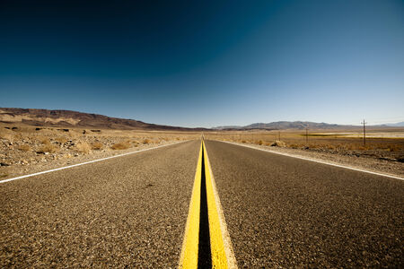 Long road, blue sky, On the way to Death Valley, It takes forever to the destination. photo
