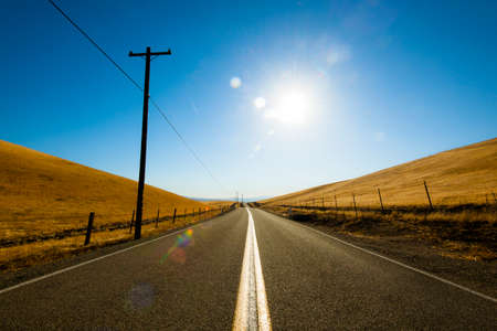 livermore: Road across country side meadow farm against sunlight Stock Photo