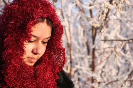 Beautiful ethnic woman, in sparkly head scarf , looks down at the ground in thought.  Blurred winter background with room for copy. Stock Photo - 295902