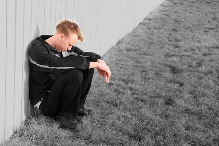 When you are sad, lonely, troubled, or depressed, your whole world seems gray.  A troubled young man sits next to a fence, feeling down about his life.